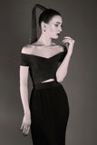 Κομψή όμορφη γυναίκα στο μαύρο φόρεμα στοκ εικόνα