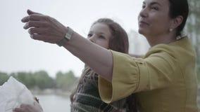 Κομψή ώριμη συνεδρίαση γυναικών στο riverbank με δύο όμορφες εγγονές της Ευτυχής χρόνος οικογενειακών εξόδων υπαίθρια απόθεμα βίντεο