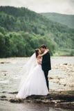 Κομψοί ευγενείς μοντέρνοι νεόνυμφος και νύφη κοντά στον ποταμό με τις πέτρες Γαμήλιο ζεύγος ερωτευμένο Στοκ Εικόνες