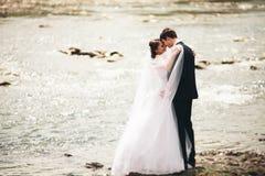 Κομψοί ευγενείς μοντέρνοι νεόνυμφος και νύφη κοντά στον ποταμό με τις πέτρες Γαμήλιο ζεύγος ερωτευμένο Στοκ φωτογραφία με δικαίωμα ελεύθερης χρήσης