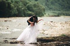 Κομψοί ευγενείς μοντέρνοι νεόνυμφος και νύφη κοντά στον ποταμό με τις πέτρες Γαμήλιο ζεύγος ερωτευμένο Στοκ εικόνες με δικαίωμα ελεύθερης χρήσης