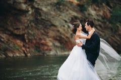 Κομψοί ευγενείς μοντέρνοι νεόνυμφος και νύφη κοντά στον ποταμό με τις πέτρες Γαμήλιο ζεύγος ερωτευμένο Στοκ Φωτογραφίες
