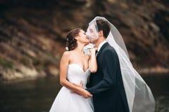 Κομψοί ευγενείς μοντέρνοι νεόνυμφος και νύφη κοντά στον ποταμό με τις πέτρες Γαμήλιο ζεύγος ερωτευμένο Στοκ εικόνα με δικαίωμα ελεύθερης χρήσης