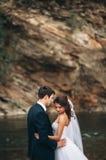 Κομψοί ευγενείς μοντέρνοι νεόνυμφος και νύφη κοντά στον ποταμό με τις πέτρες Γαμήλιο ζεύγος ερωτευμένο Στοκ Φωτογραφία