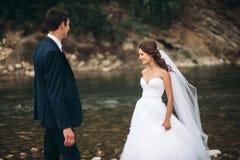 Κομψοί ευγενείς μοντέρνοι νεόνυμφος και νύφη κοντά στον ποταμό με τις πέτρες Γαμήλιο ζεύγος ερωτευμένο Στοκ Εικόνα