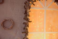 Κομψοί κλάδοι με το φωτισμένο παράθυρο γιρλαντών Στοκ Φωτογραφίες
