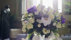 Κομψοί μοντέρνοι διακοσμημένοι πίνακες δεξίωσης γάμου με τα γυαλιά και λουλούδια στην κινηματογράφηση σε πρώτο πλάνο βάζων φιλμ μικρού μήκους