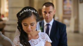 Κομψοί νύφη και νεόνυμφος που φορούν τα μπλε χέρια εκμετάλλευσης κοστουμιών που περπατούν στην παλαιά εκκλησία φιλμ μικρού μήκους