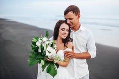 Κομψοί πανέμορφοι νύφη και νεόνυμφος που περπατούν στην ωκεάνια παραλία κατά τη διάρκεια του χρόνου ηλιοβασιλέματος στοκ φωτογραφία με δικαίωμα ελεύθερης χρήσης