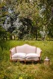 Κομψός άσπρος καναπές στον κήπο Στοκ εικόνα με δικαίωμα ελεύθερης χρήσης
