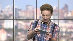 Κομψός έφηβος που παίζει το κινητό παιχνίδι φιλμ μικρού μήκους