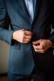 Κομψός ανθρώπινος παραδίδει το μαύρο κοστούμι κουμπώνοντας επάνω Στοκ Φωτογραφία