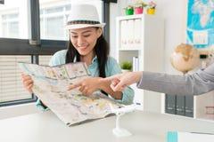 Κομψός ελκυστικός θηλυκός ταξιδιώτης που δείχνει το χάρτη στοκ εικόνες