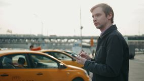 Κομψός επιχειρηματίας που ελέγχει την εφαρμογή app ταξί στο κινητό τηλέφωνο περπατώντας έξω από τον αερολιμένα, πεπειραμένο αρσεν φιλμ μικρού μήκους