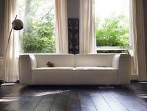 Κομψός καναπές πριν από ένα παράθυρο στοκ φωτογραφία με δικαίωμα ελεύθερης χρήσης