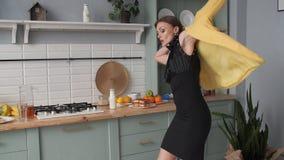 Κομψός καταφερτζής κατανάλωσης γυναικών brunette στην κουζίνα και χορός απόθεμα βίντεο