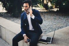 Κομψός νέος επιχειρηματίας που εργάζεται έξω με το κινητό lap-top υπέρ Όμορφο άτομο που χρησιμοποιεί το σύγχρονο smartphone για τ Στοκ Εικόνες
