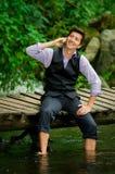 Κομψός νεαρός άνδρας που χρησιμοποιεί το τηλέφωνο κυττάρων σε μια λίμνη Στοκ φωτογραφίες με δικαίωμα ελεύθερης χρήσης