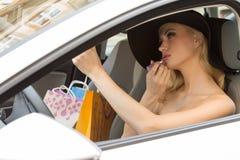 Κομψός ξανθός με το κραγιόν στο αυτοκίνητο Στοκ Εικόνα