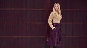 Κομψός ξανθός Georgeous στο φωτεινό φόρεμα στο ξύλινο υπόβαθρο Στοκ φωτογραφίες με δικαίωμα ελεύθερης χρήσης