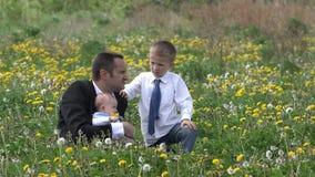 Κομψός πατέρας με το παιδί και το μωρό στον τομέα ανθών, επιχειρηματίας και γιος, άτομο στο άτομο συζήτηση, σχέση οικοδόμησης απόθεμα βίντεο