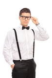 Κομψός τύπος που κρατά τα γυαλιά του και που εξετάζει τη κάμερα Στοκ φωτογραφία με δικαίωμα ελεύθερης χρήσης