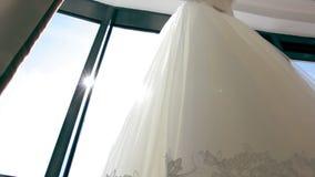 Κομψότητα, όμορφος, γαμήλιο φόρεμα στο παράθυρο απόθεμα βίντεο