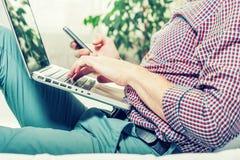 Κομψό άτομο επιχειρησιακών πολλαπλών καθηκόντων πολυμέσων που χρησιμοποιεί τις συσκευές στο σπίτι Στοκ Εικόνα