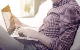 Κομψό άτομο επιχειρησιακών πολλαπλών καθηκόντων πολυμέσων που χρησιμοποιεί τις συσκευές στο σπίτι Στοκ φωτογραφία με δικαίωμα ελεύθερης χρήσης