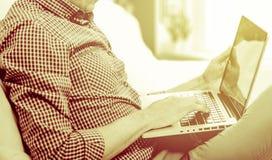 Κομψό άτομο επιχειρησιακών πολλαπλών καθηκόντων πολυμέσων που χρησιμοποιεί τις συσκευές στο σπίτι Στοκ φωτογραφίες με δικαίωμα ελεύθερης χρήσης