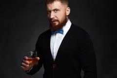 Κομψό άτομο στο κοστούμι και δεσμός που πίνει ένα ουίσκυ στο στούντιο στοκ φωτογραφία