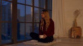 Κομψό ήρεμο κορίτσι που απολαμβάνεται το φλυτζάνι του τσαγιού από το παράθυρο