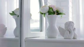Κομψό βάζο με τα λουλούδια και statuette Cupid φιλμ μικρού μήκους