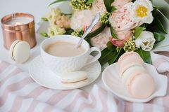 Κομψό γλυκό επιδόρπιο macarons, φλιτζάνι του καφέ και χρωματισμένη κρητιδογραφία μπεζ ανθοδέσμη λουλουδιών στοκ εικόνα με δικαίωμα ελεύθερης χρήσης