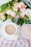 Κομψό γλυκό επιδόρπιο macarons, φλιτζάνι του καφέ και χρωματισμένη κρητιδογραφία μπεζ ανθοδέσμη λουλουδιών στοκ φωτογραφίες