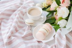 Κομψό γλυκό επιδόρπιο macarons, φλιτζάνι του καφέ και χρωματισμένη κρητιδογραφία μπεζ ανθοδέσμη λουλουδιών στοκ εικόνες