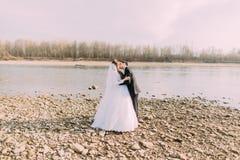 Κομψό ευγενές μοντέρνο φίλημα νεόνυμφων και νυφών κοντά στον ποταμό με τις πέτρες στοκ φωτογραφίες