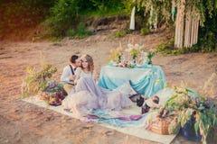 Κομψό ζεύγος Boho ερωτευμένο η νύφη και ο νεόνυμφος Πικ-νίκ γαμήλιας έμπνευσης υπαίθρια, με τον πίνακα γευμάτων και το ντεκόρ τυρ στοκ εικόνα