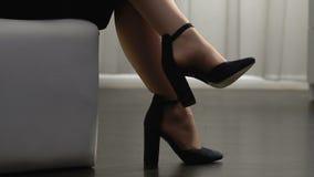 Κομψό θηλυκό στα υψηλά τακούνια που κάθεται με τα πόδια που διασχίζονται, καθιερώνοντα τη μόδα παπούτσια, μόδα απόθεμα βίντεο