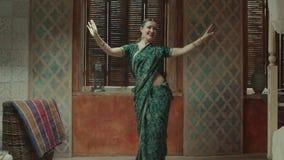 Κομψό θηλυκό στη Sari που εκτελεί τον ινδικό χορό φιλμ μικρού μήκους