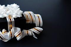 Κομψό κιβώτιο δώρων που τυλίγεται στην άσπρη ριγωτή κορδέλλα στο μαύρο κατασκευασμένο υπόβαθρο r r ημέρα πατέρα, μαύρη στοκ εικόνα με δικαίωμα ελεύθερης χρήσης