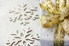 Κομψό κιβώτιο δώρων που τυλίγεται στο γκρίζο ασημένιο έγγραφο με τη χρυσή κορδέλλα σημείων Πόλκα στις χιονώδεις νιφάδες χιονιού υ Στοκ Φωτογραφίες