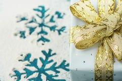 Κομψό κιβώτιο δώρων που τυλίγεται στο γκρίζο ασημένιο έγγραφο με τη χρυσή κορδέλλα σημείων Πόλκα στο χιονώδες υπόβαθρο με τις μπλ Στοκ Εικόνα
