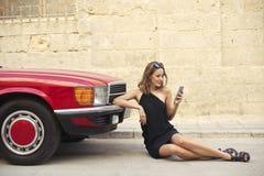 Κομψό κορίτσι που χρησιμοποιεί ένα smartphone δίπλα σε ένα αυτοκίνητο Στοκ φωτογραφίες με δικαίωμα ελεύθερης χρήσης