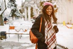 Κομψό μαύρο κορίτσι σε μια χειμερινή πόλη στοκ εικόνα