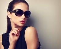 Κομψό νέο θηλυκό πρότυπο στην καθιερώνουσα τη μόδα τοποθέτηση γυαλιών ηλίου Τρύγος στοκ εικόνες