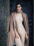 Κομψό παλτό mocha μόδας πρότυπο φορώντας μακρύ, που θέτει πριν από μια πόρτα Στοκ Εικόνες