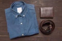 Κομψό σύνολο: καφετιά ζώνη δέρματος, μπλε πουκάμισο, καφετί πορτοφόλι, στο θόριο Στοκ Φωτογραφία