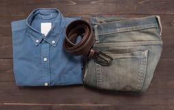 Κομψό σύνολο: καφετιά ζώνη ατόμων ` s, Jean, μπλε πουκάμισο, στο ξύλινο β Στοκ Εικόνες