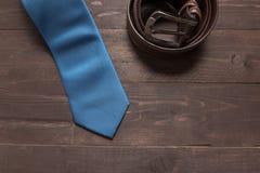 Κομψό σύνολο: μπλε δεσμός, καφετιά ζώνη δέρματος, στο ξύλινο backgro Στοκ φωτογραφία με δικαίωμα ελεύθερης χρήσης